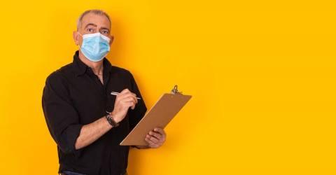 Medewerker met mondkapje heeft een pen met schrijfblok in de hand